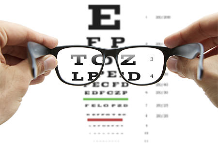 Looking through eyeglasses at eye chart